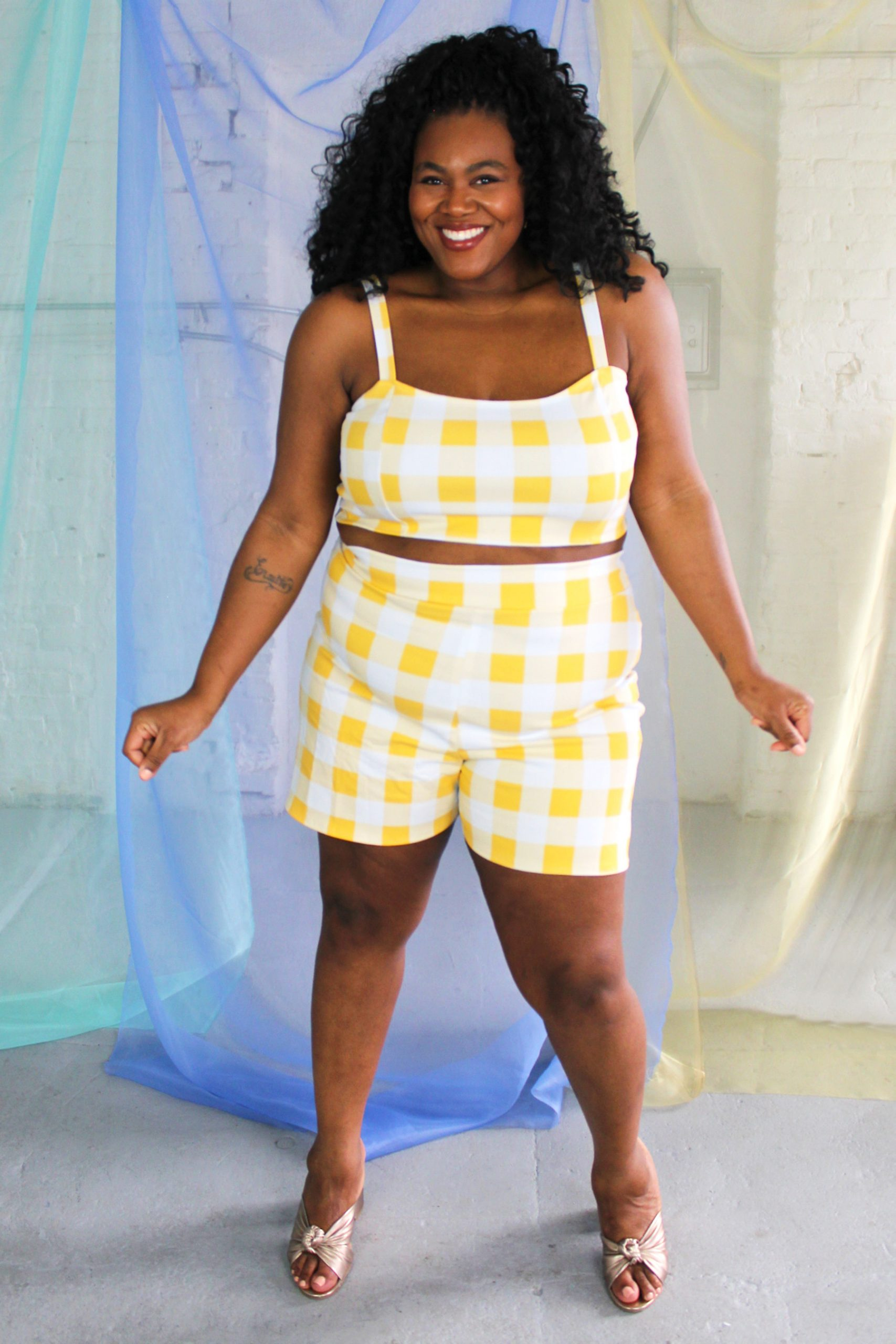 Black plus size female model with curls wearing yellow and white check crop top and high waist shorts ethically handmade
