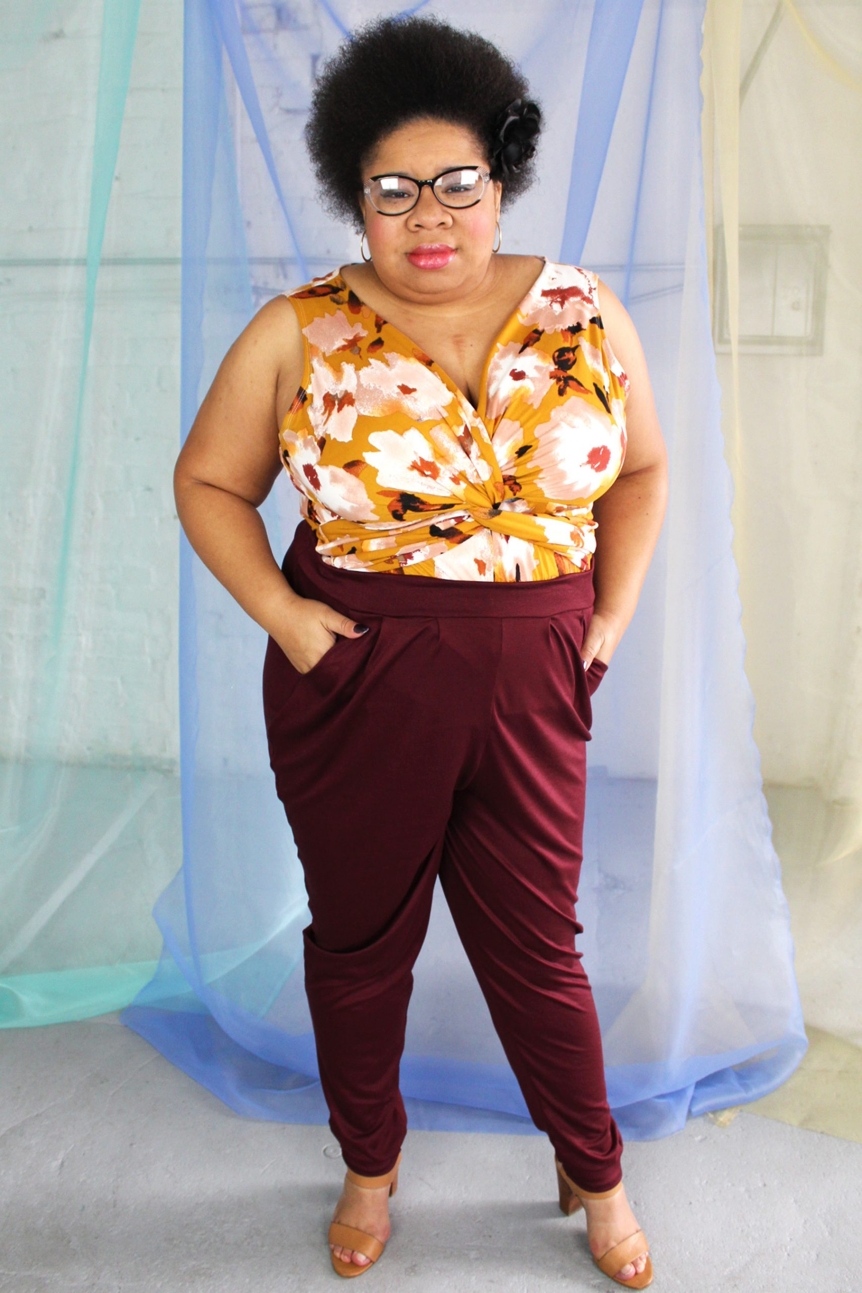 Plus size black model with afro + glasses wearing wine maroon pants with pockets and mustard floral twist detail jersey tank
