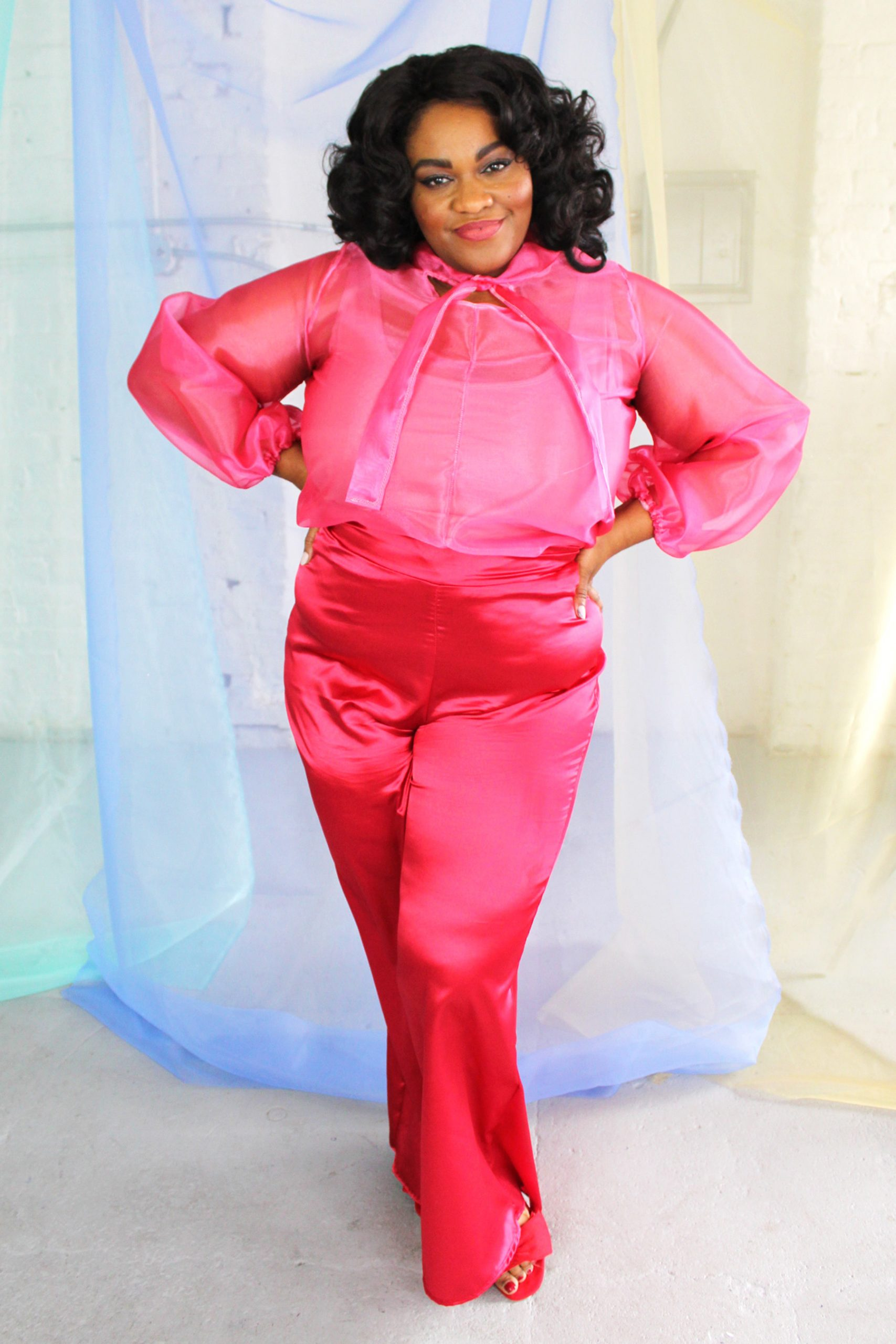 Plus size black model with curly hair wearing pink organza blouse with neck tie + bell sleeves with red satin pants handmade