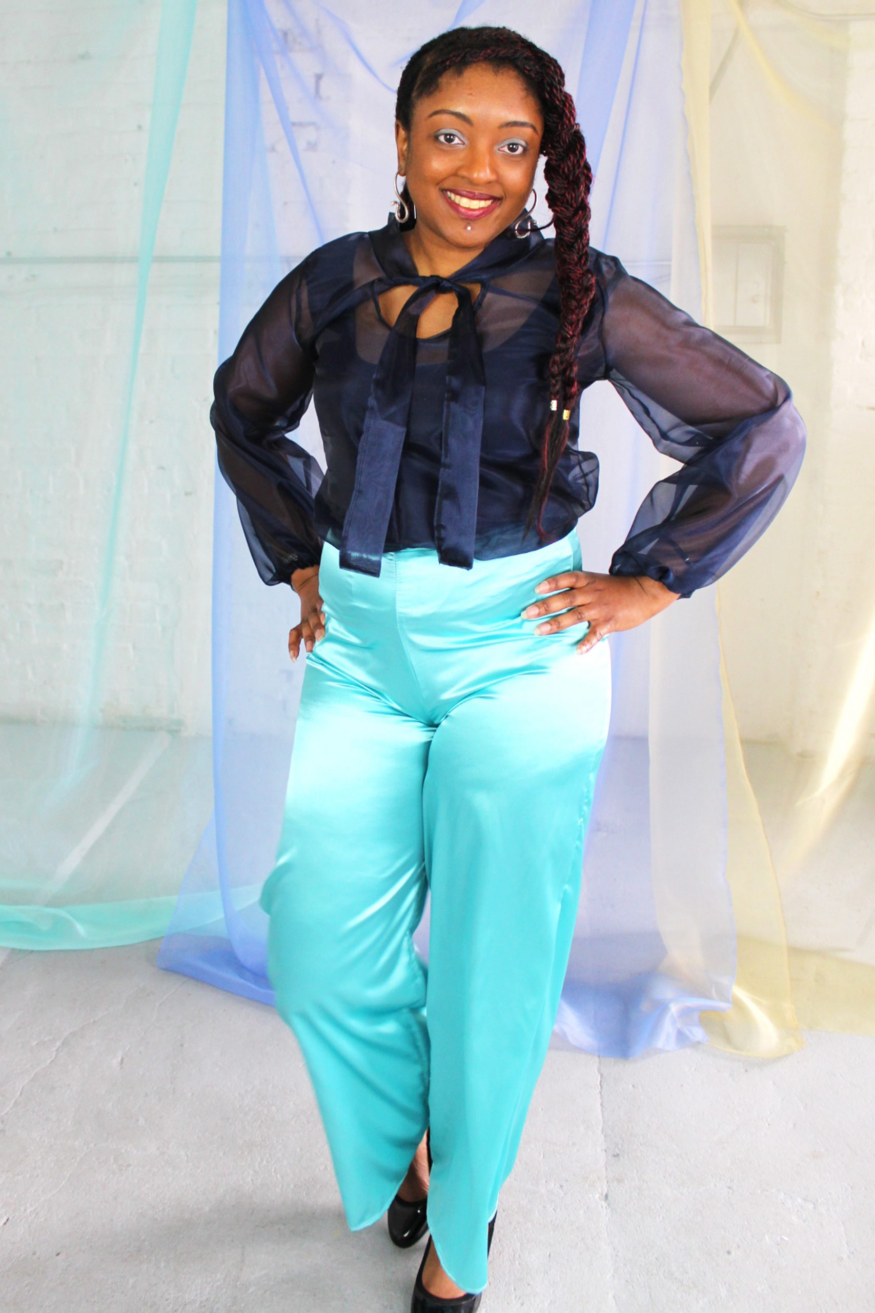 Straight size black model with braided hair wearing navy organza blouse with neck tie + bell sleeves with seafoam satin pants
