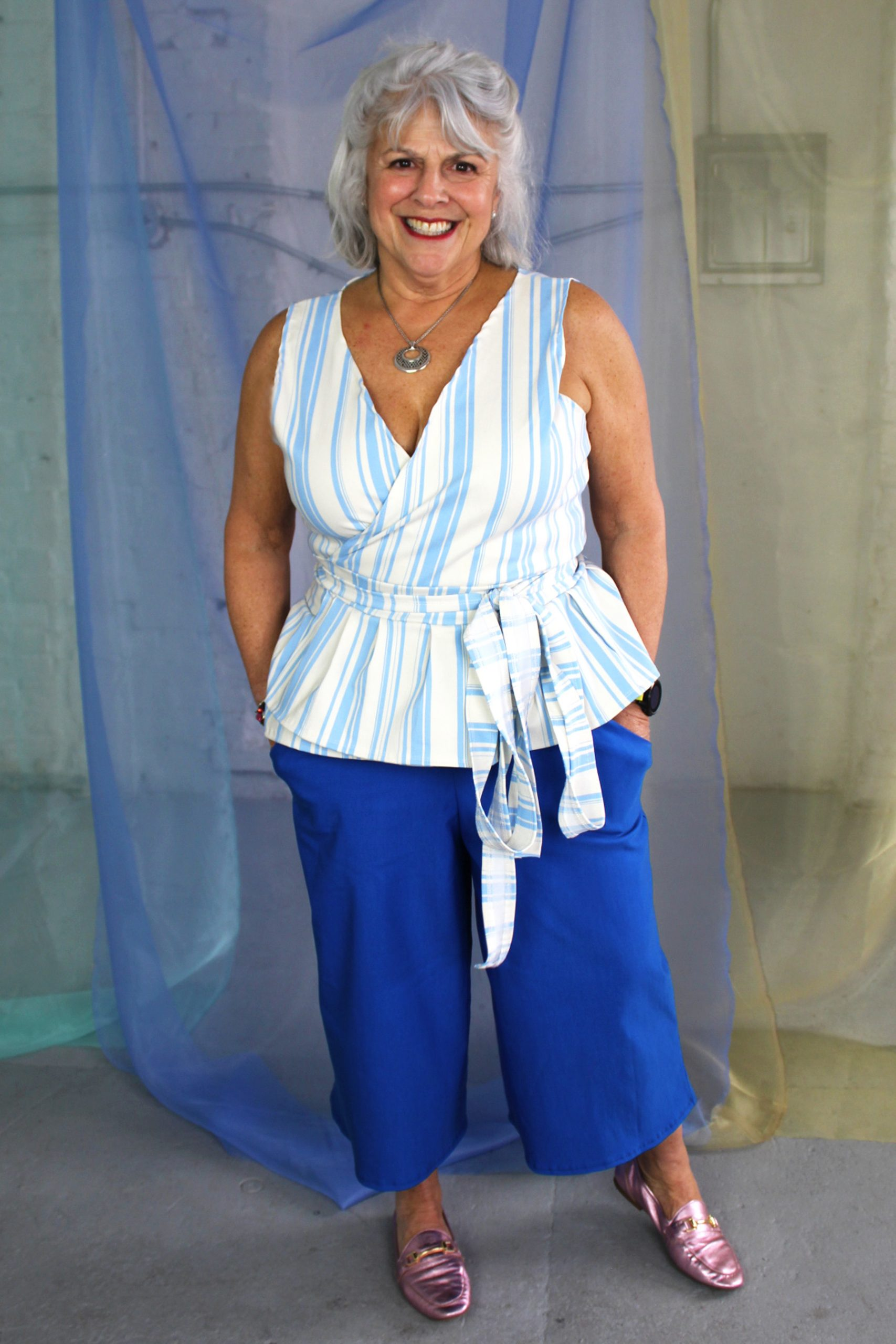 Inbetweenie size petite white mature model wearing blue capri pants with pockets and white and blue striped wrap top