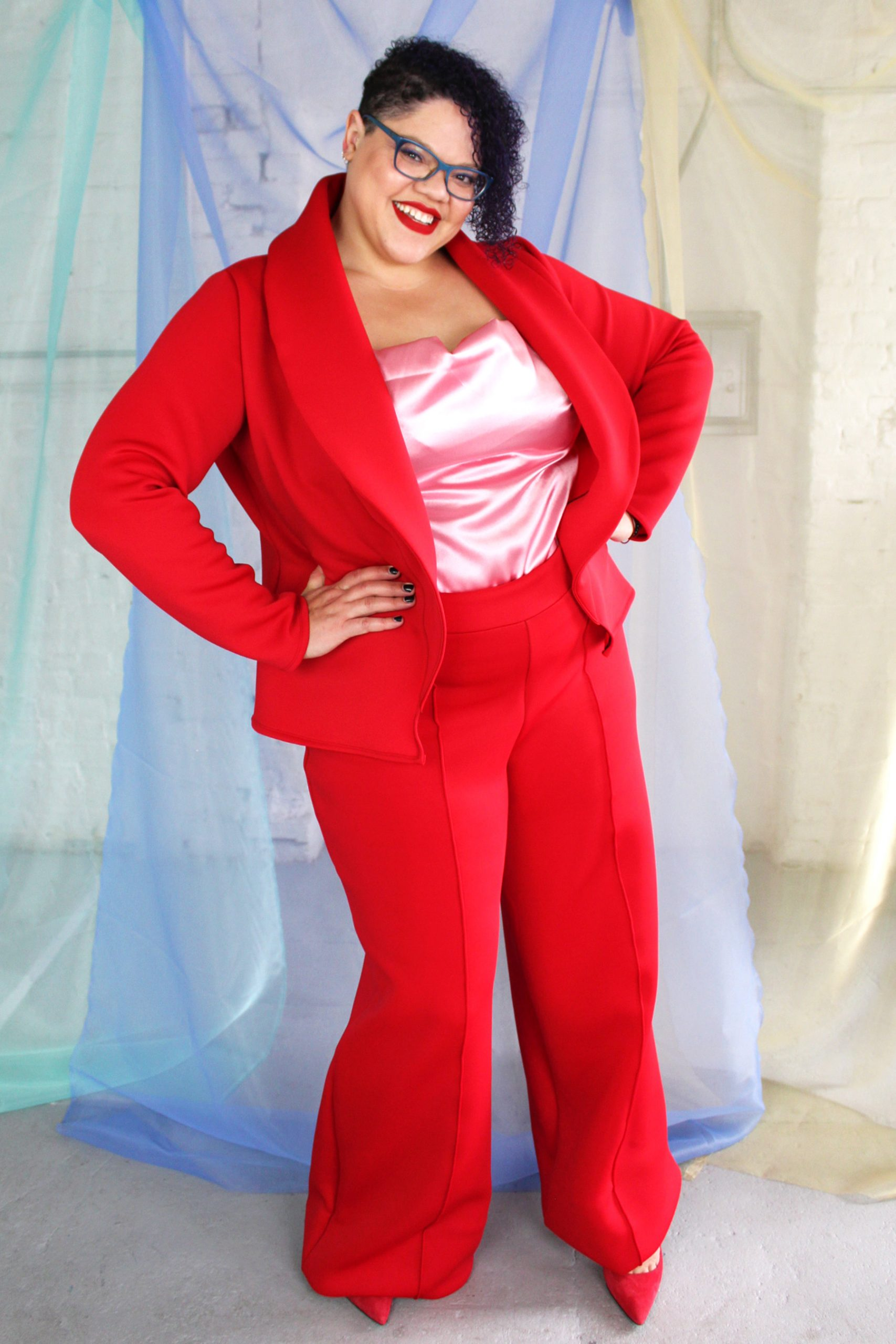 Plus size tall black model with short curly hair wearing red suit and pink satin camisole, ethically handmade in NYC