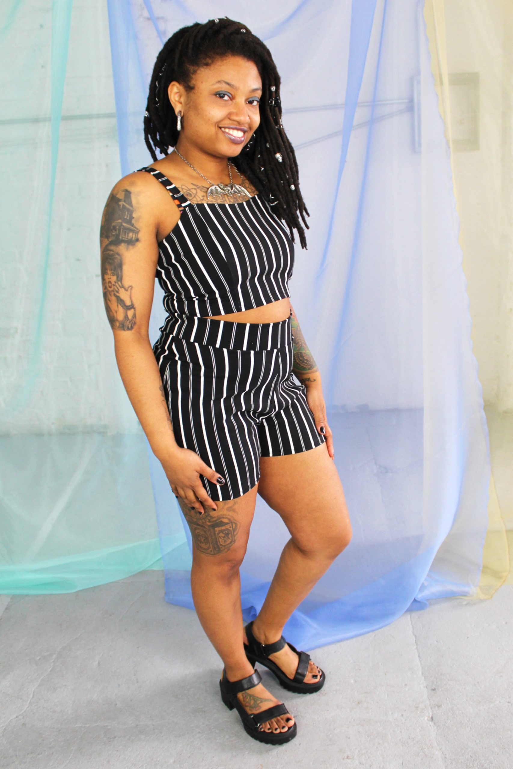Black straight size female model with locs wearing black and white striped crop top and high waist shorts ethically handmade
