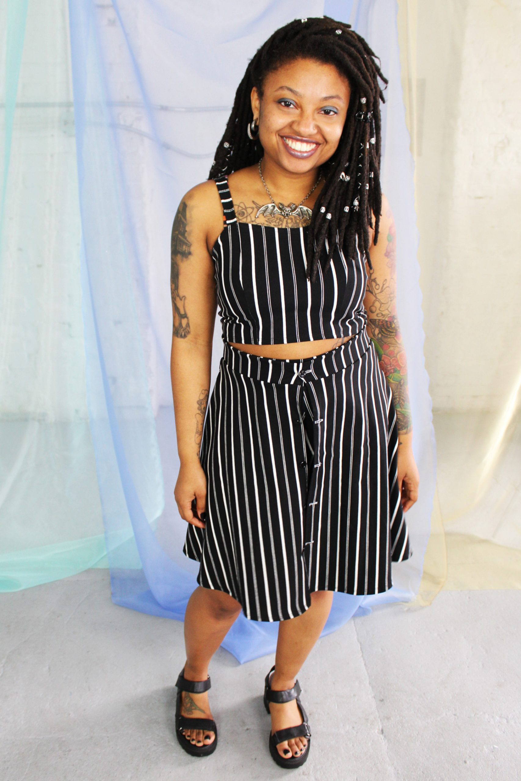 Black smiling straight size model with locs modeling black and white striped crop top and skirt - ethically handmade in NYC