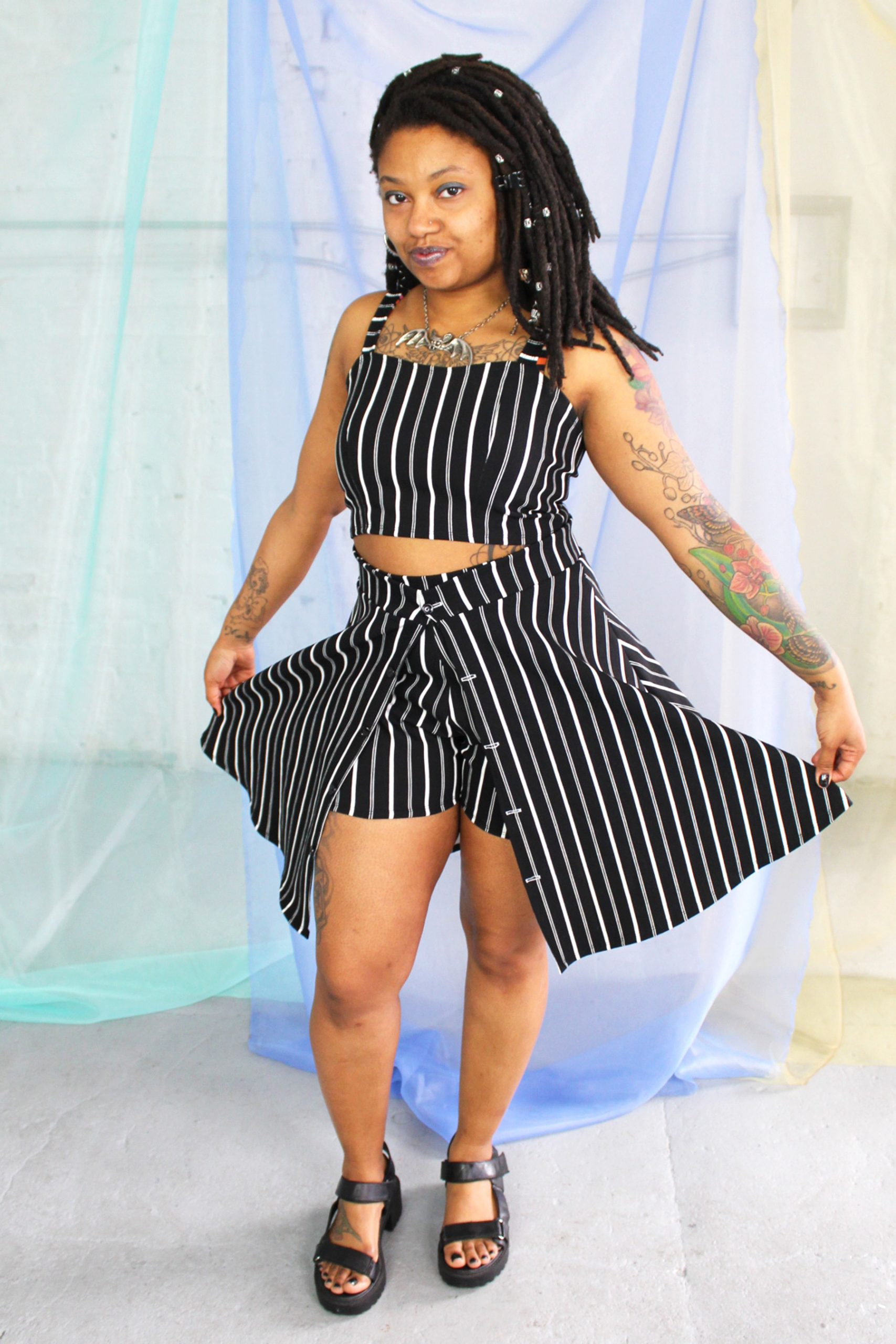 Black straight size model with locs modeling black and white striped crop top, shorts, and over skirt - ethically made in NYC