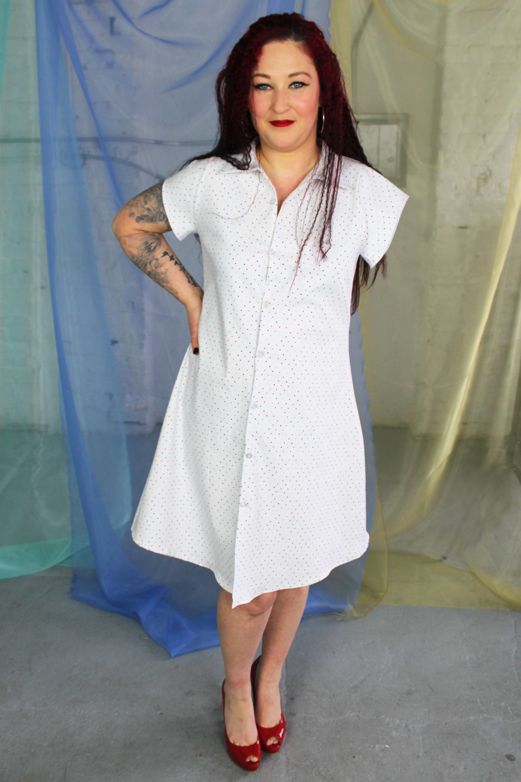 Smirking straight size white female model with one arm modeling white multi color polka dot button front collared shirt dress