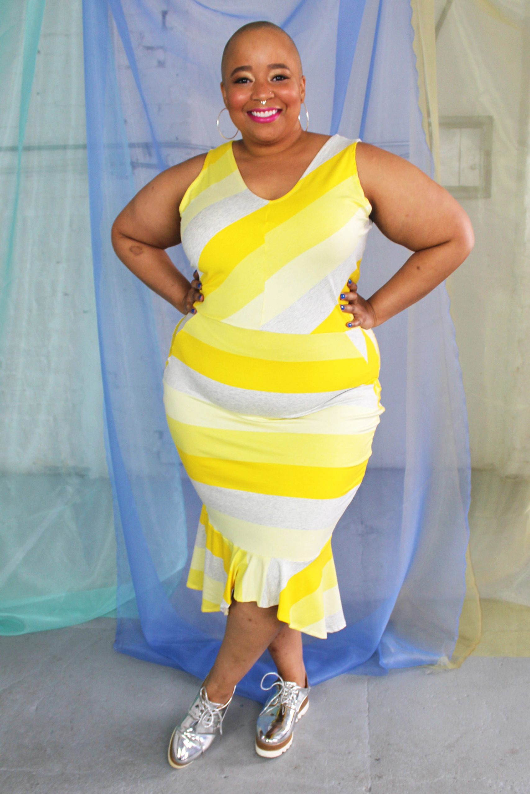 Yellow v-neck striped dress with pencil skirt and ruffle hemline modeled by plus size black bald model.