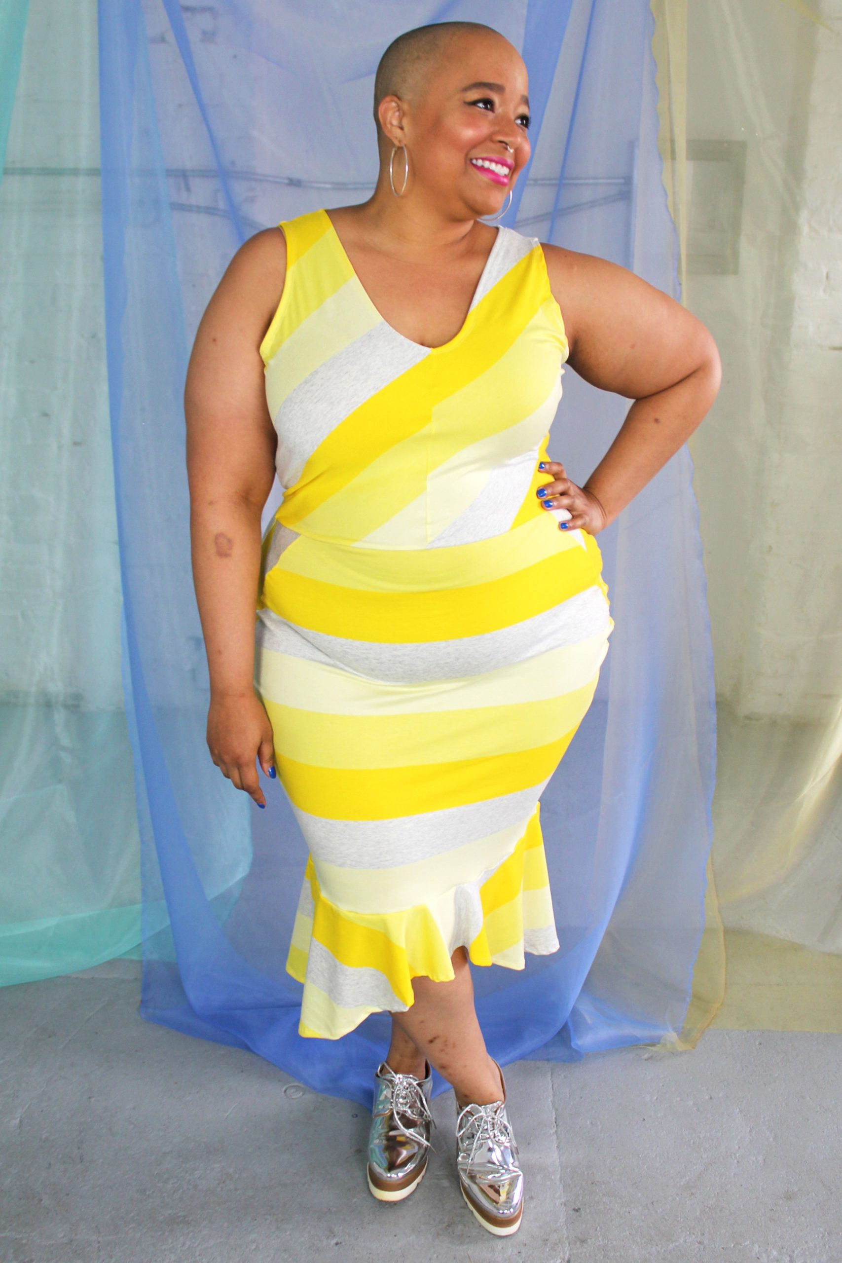 Smiling black plus size model wearing yellow Nadine striped jersey dress with a v-neck and ruffle at bottom of fitted skirt.
