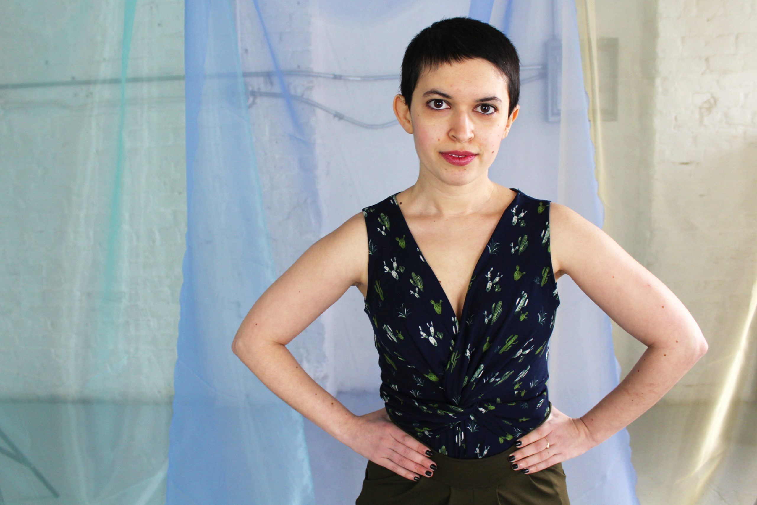 Non binary white petite model with short brunette pixie cut modeling navy cactus print twist detail tank top with olive pants