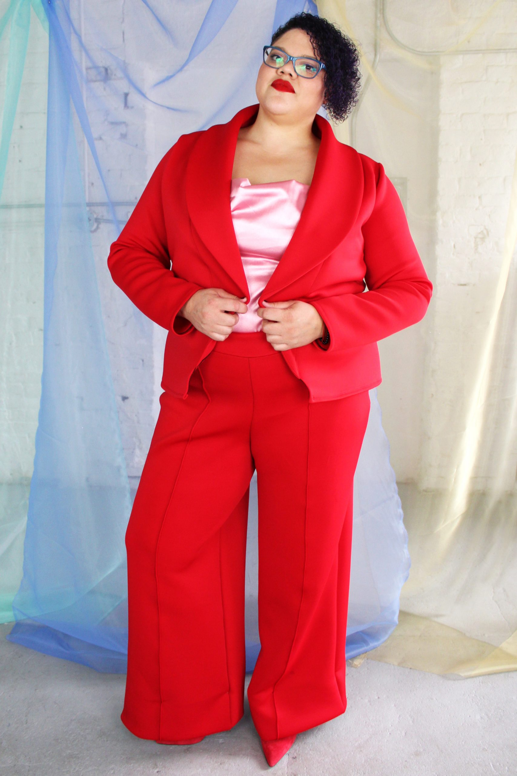 Confident plus size tall black model with curly short hair wearing red suit and pink satin camisole, ethically made in NYC