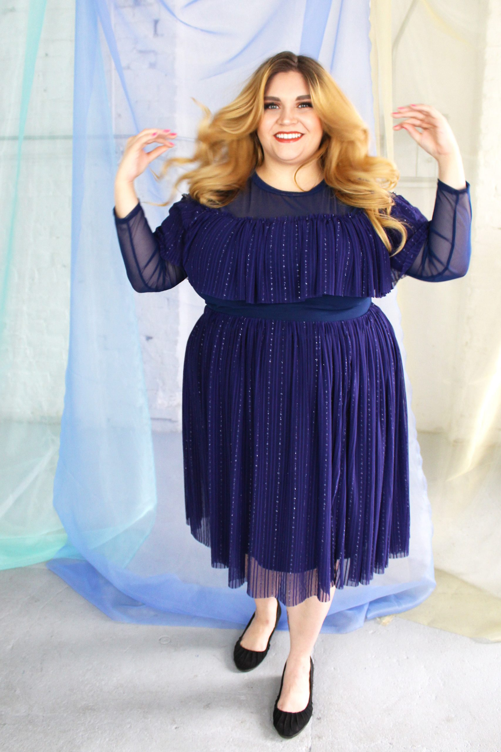 White blonde plus size model wearing navy classic blue mesh high neck long sleeved top with ruffle and matching skirt