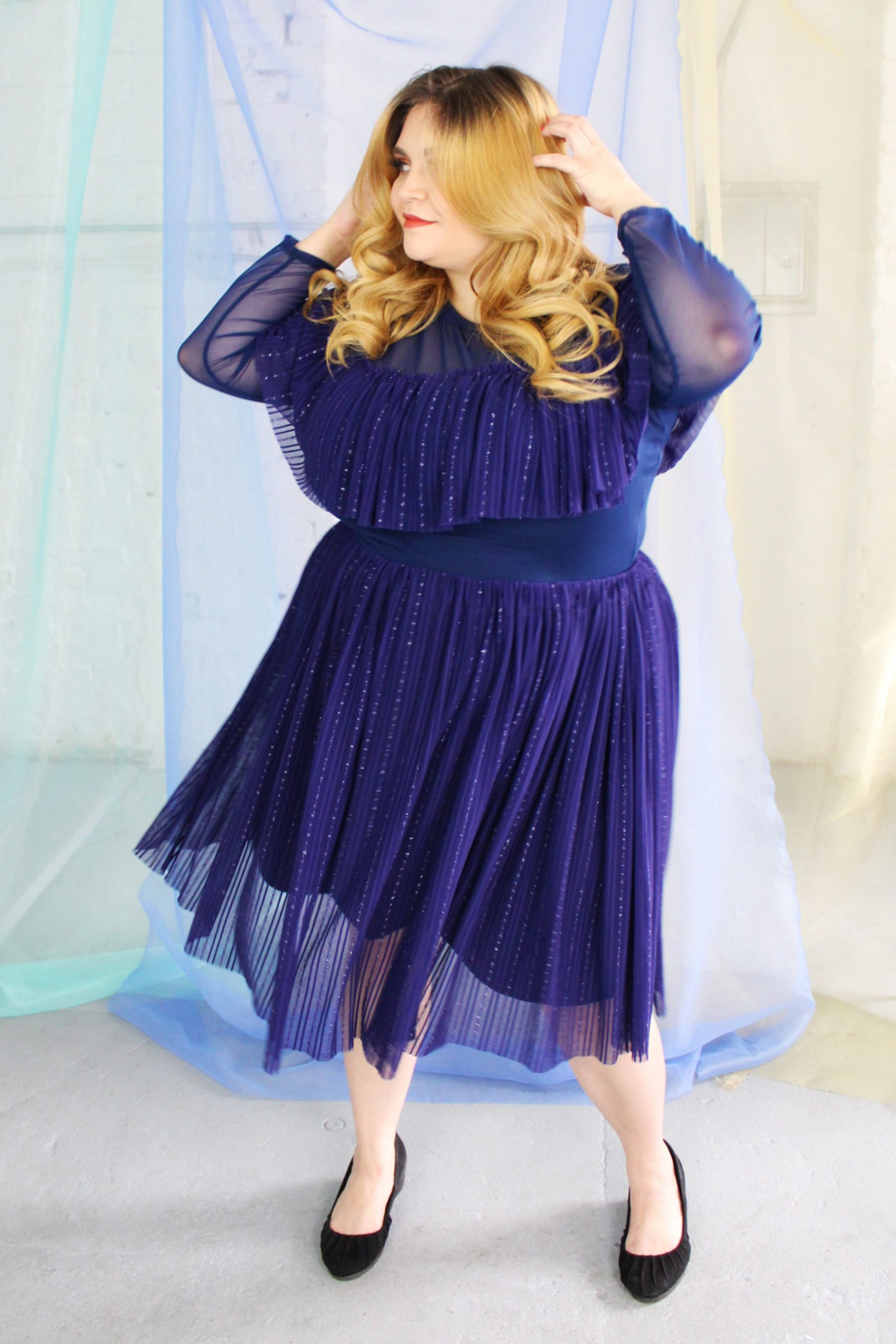 White blonde plus size model wearing navy classic blue mesh skirt smiling and happy, with matching long sleeve ruffle top