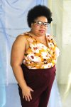 Plus size black model with afro and glasses modeling jersey tank with twist detail in mustard and wine color floral print