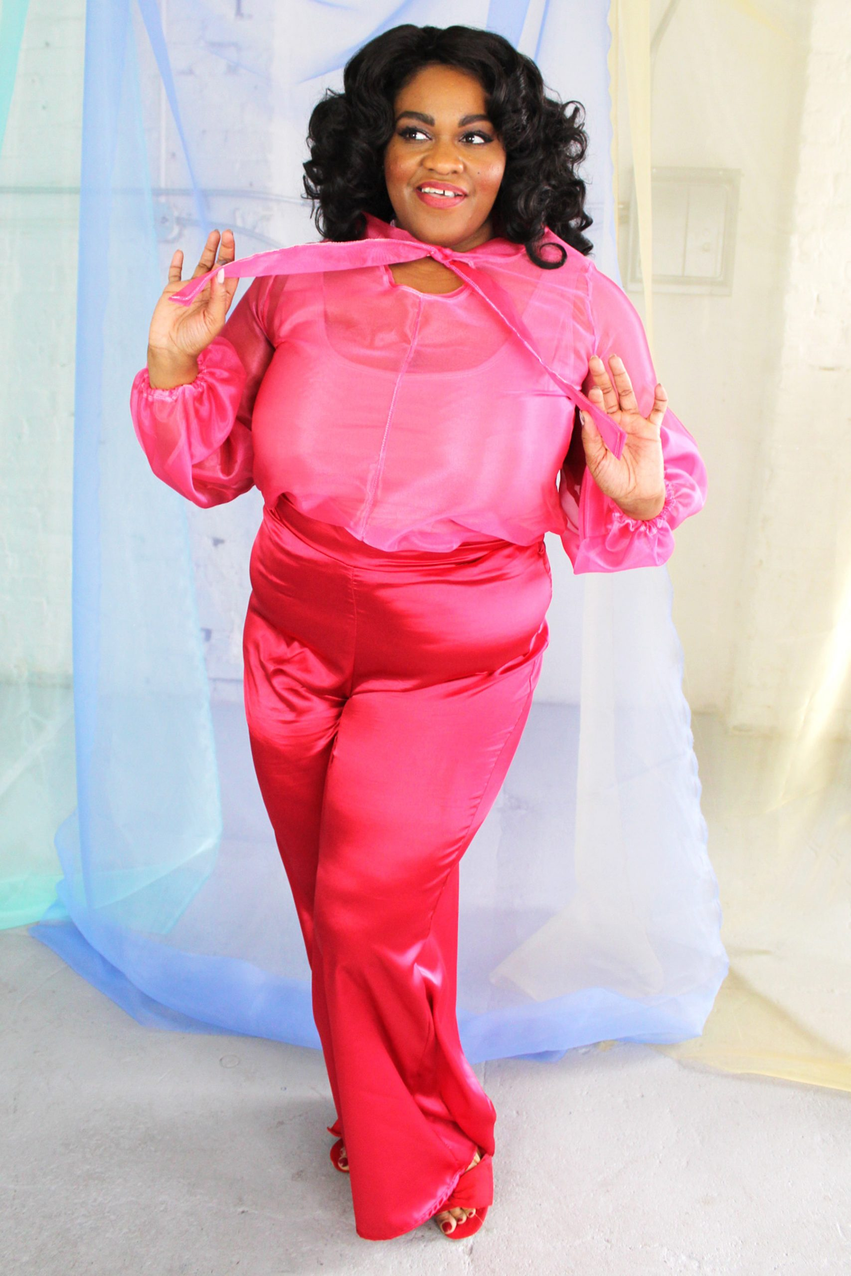 Plus size black model with curly hair wearing pink organza blouse and red satin wide leg pants, ethically handmade in NYC