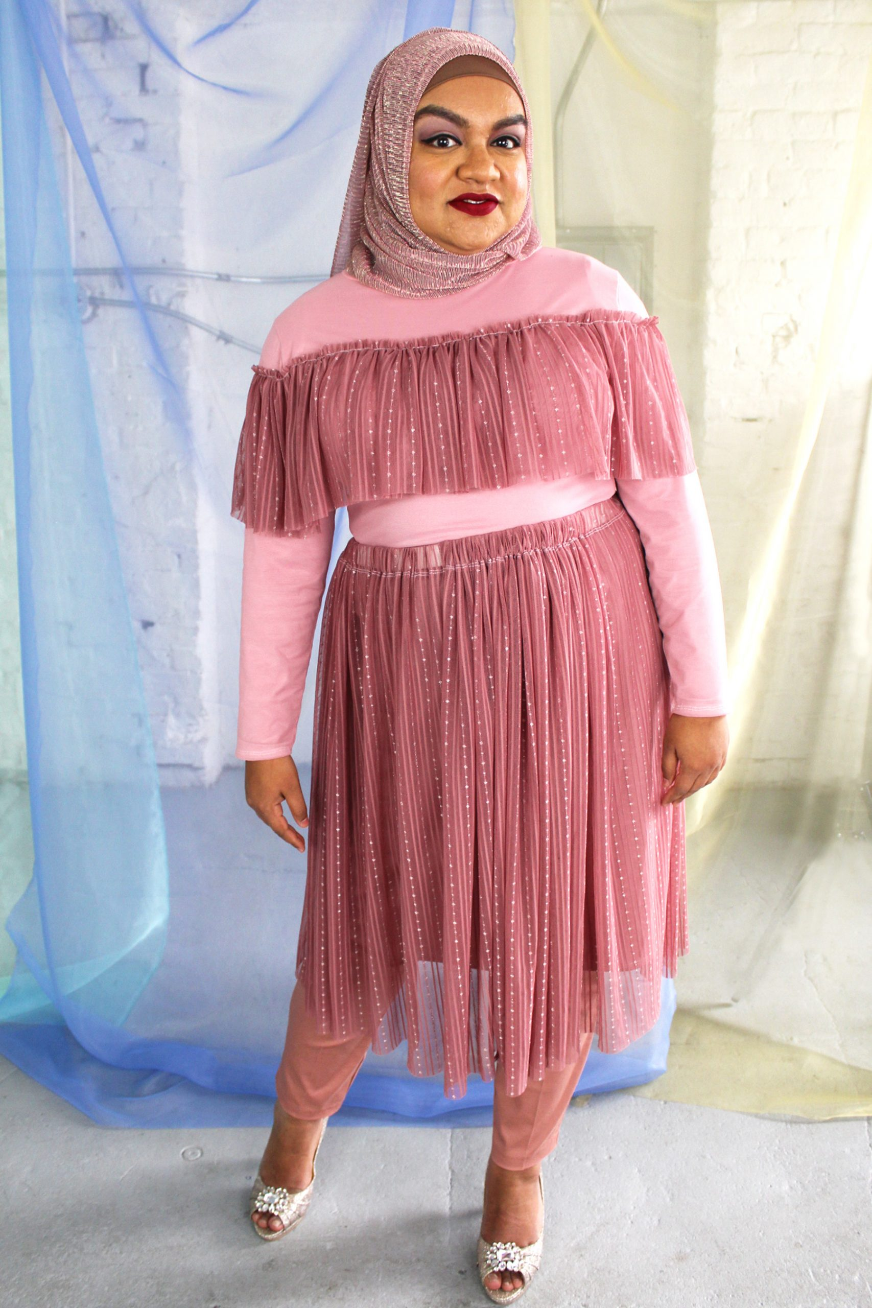Hijabi plus size model wearing dusty rose pink mesh skirt smiling and happy, with matching long sleeve ruffle top