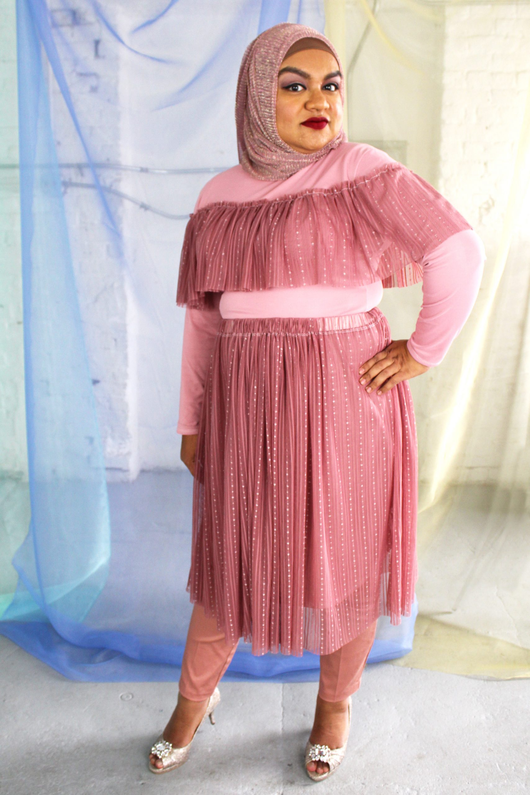 Hijabi plus size model wearing dusty rose pink mesh high neck long sleeved top with ruffle and matching skirt