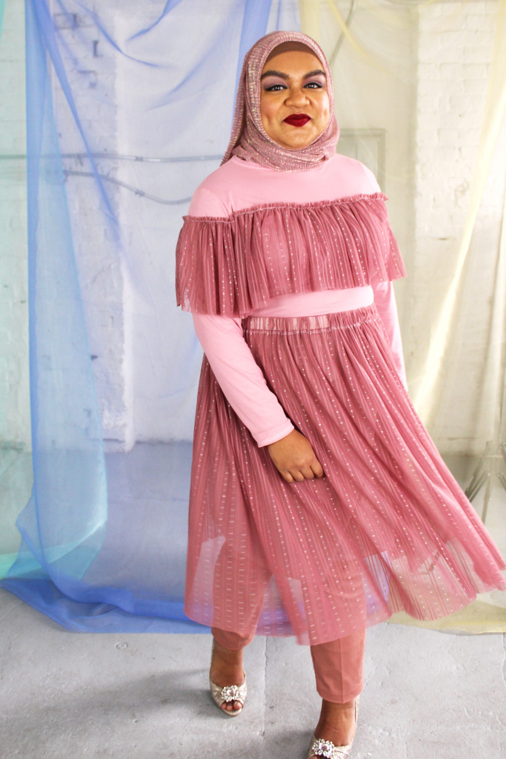 Hijabi plus size model wearing dusty rose pink mesh skirt twirling and happy, with matching long sleeve ruffle top