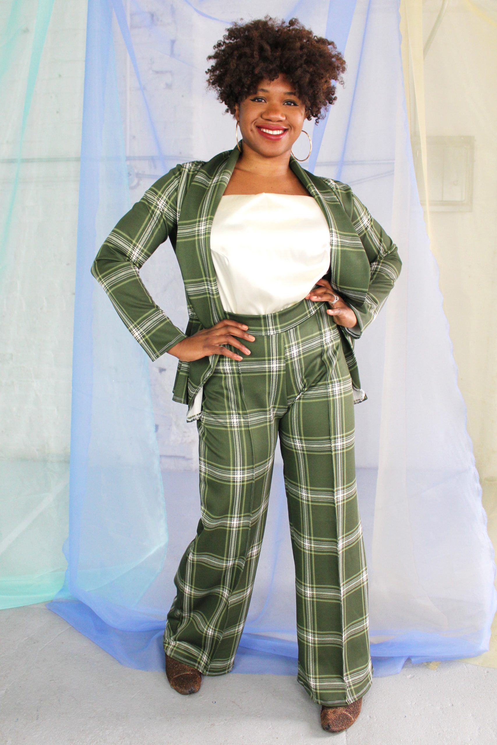 Confident straight size black model with curly short hair wearing green plaid suit and cream satin camisole, handmade in NYC