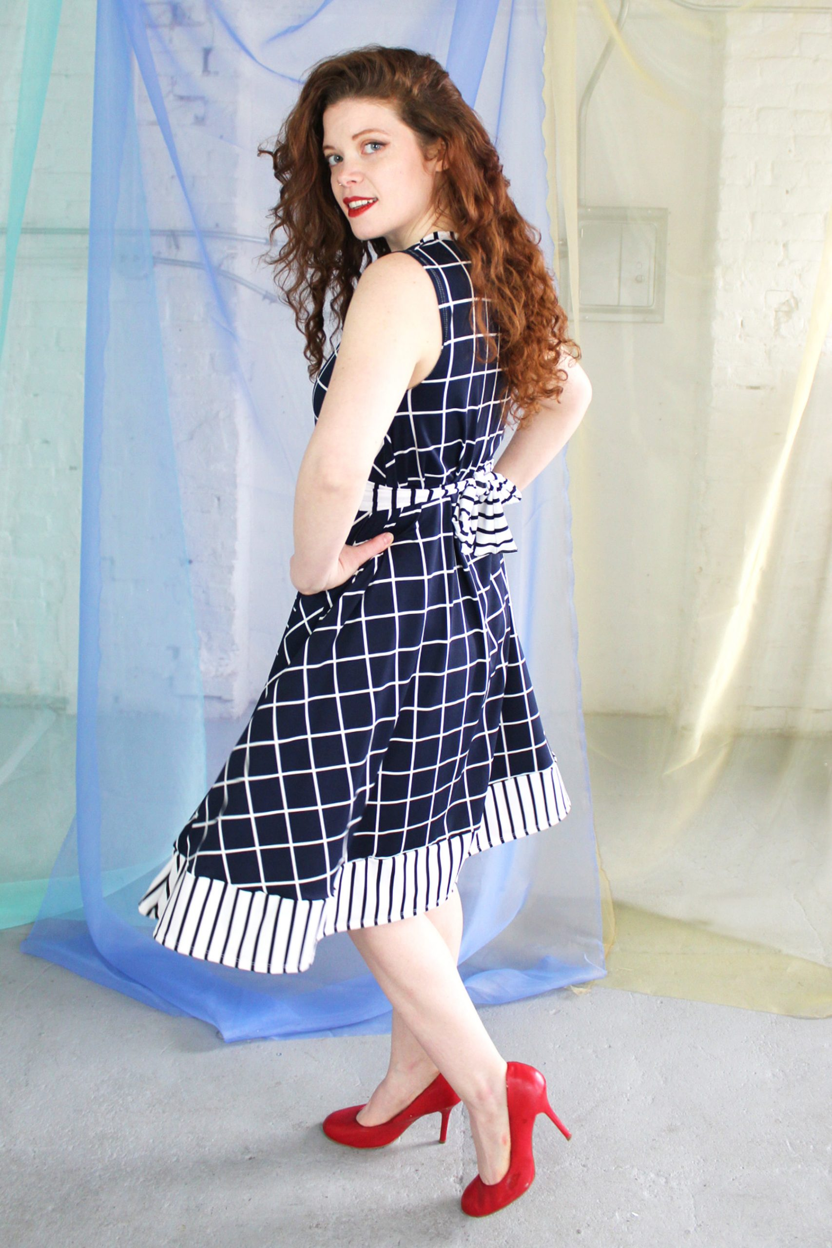 Straight size white redhead model wearing dark navy and white swing dress with striped trim and waist belt, handmade in NYC