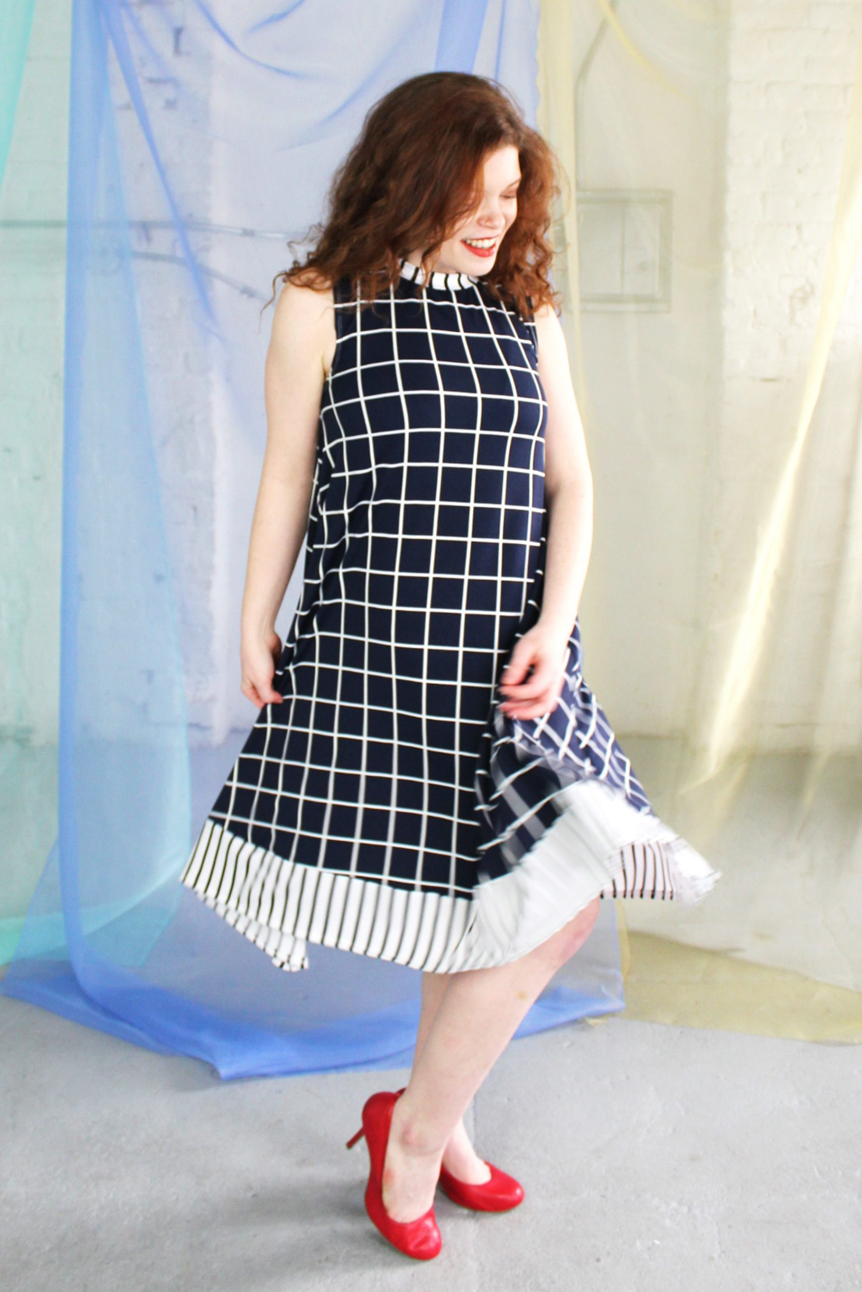 Straight size white redhead model wearing dark navy and white swing dress with striped trim, ethically handmade in NYC