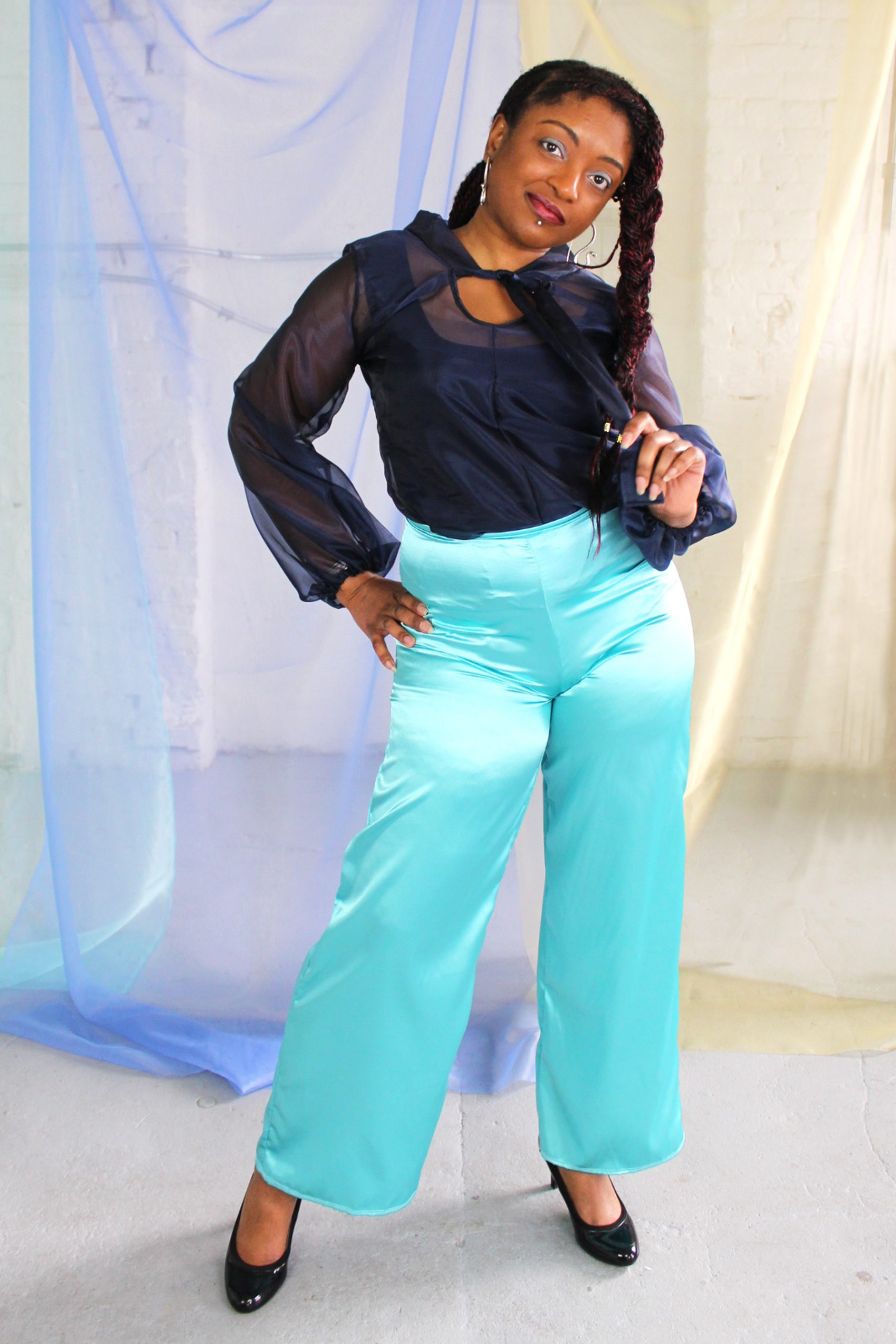 Straight size black model with braid wearing navy organza blouse and seafoam blue green satin wide leg pants, handmade in NYC
