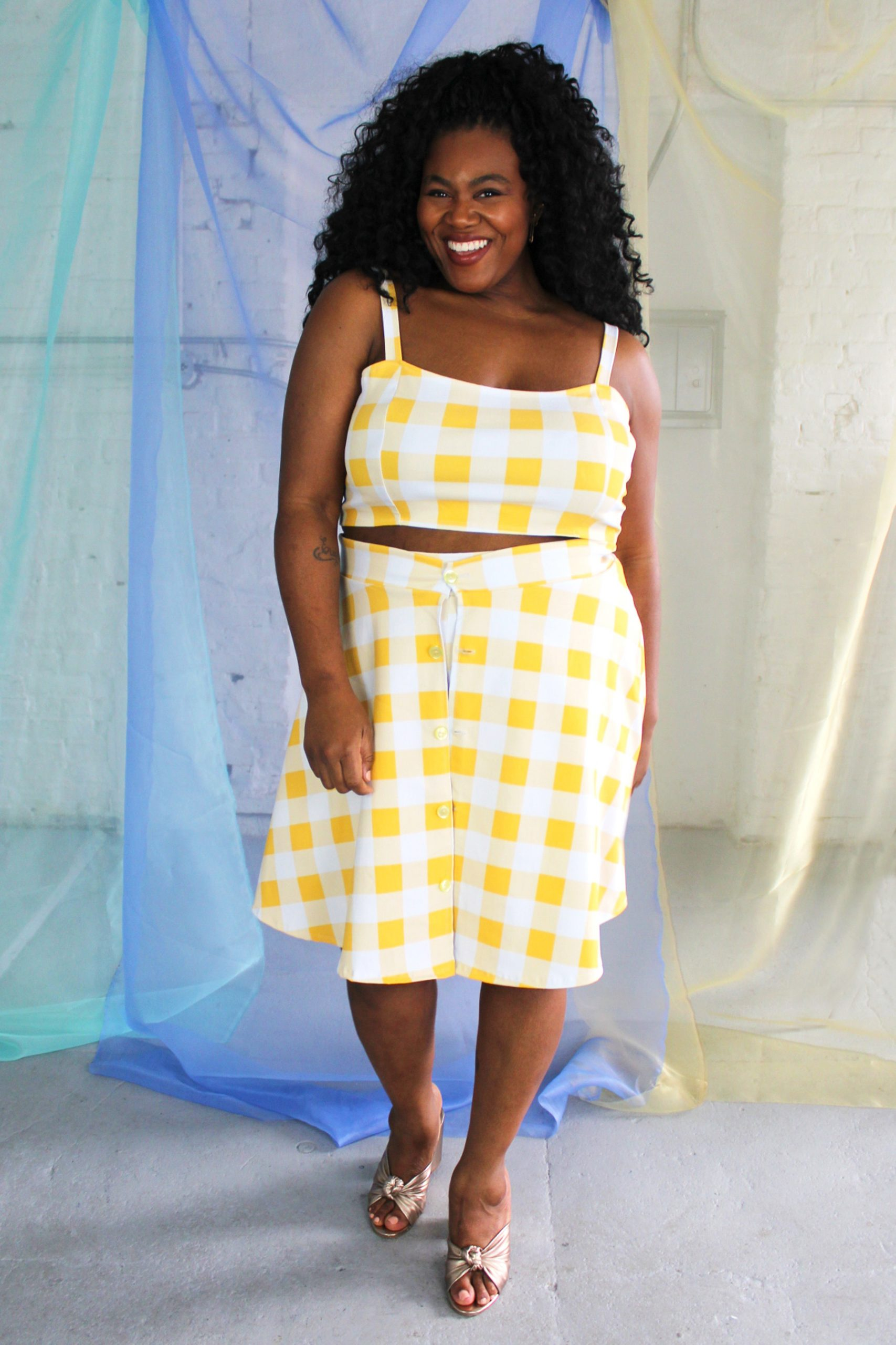 Black smiling plus size model modeling yellow and white check crop top, shorts, and over skirt - ethically handmade in NYC