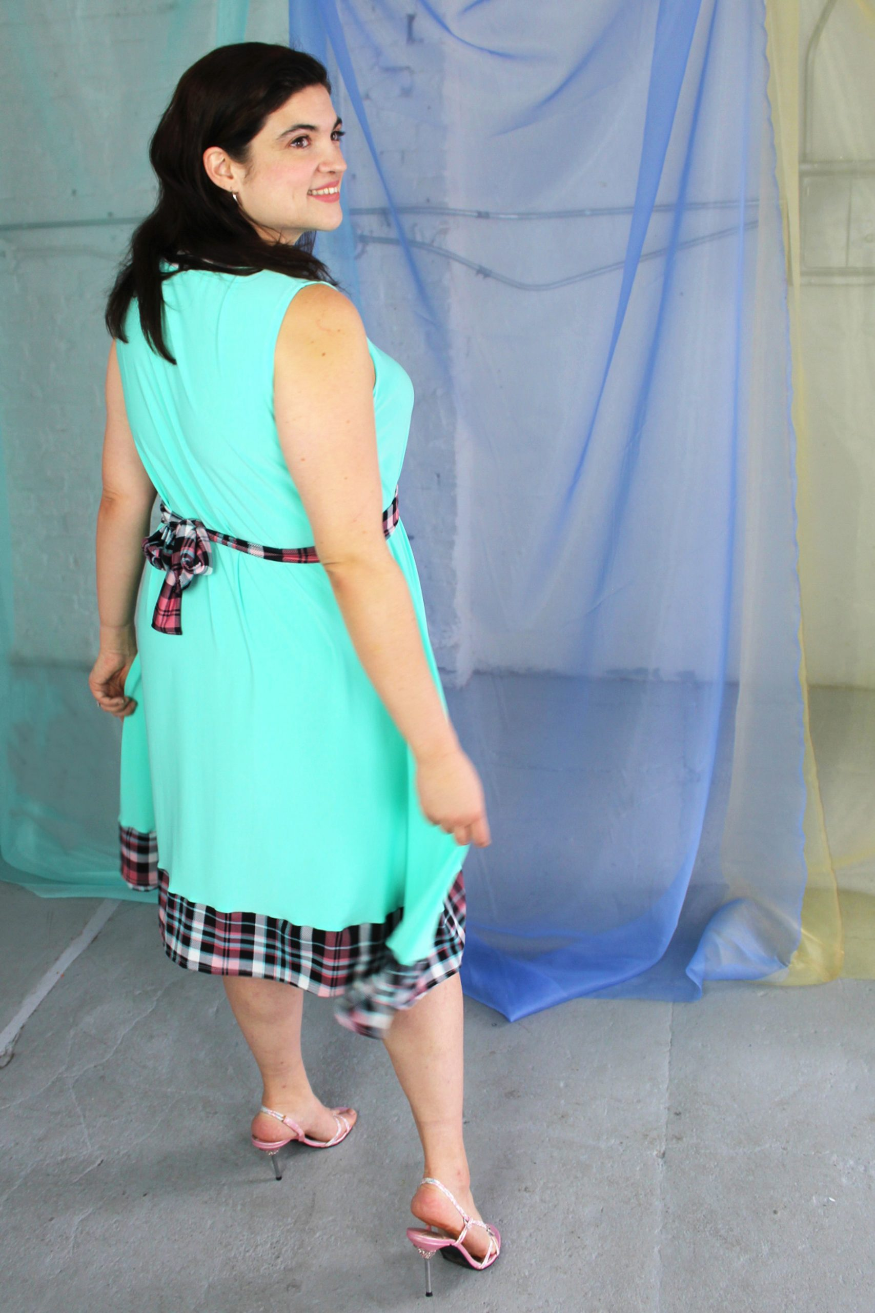 Inbetweenie white brunette model wearing seafoam blue green swing dress with pink plaid trim and waist belt, handmade in NYC