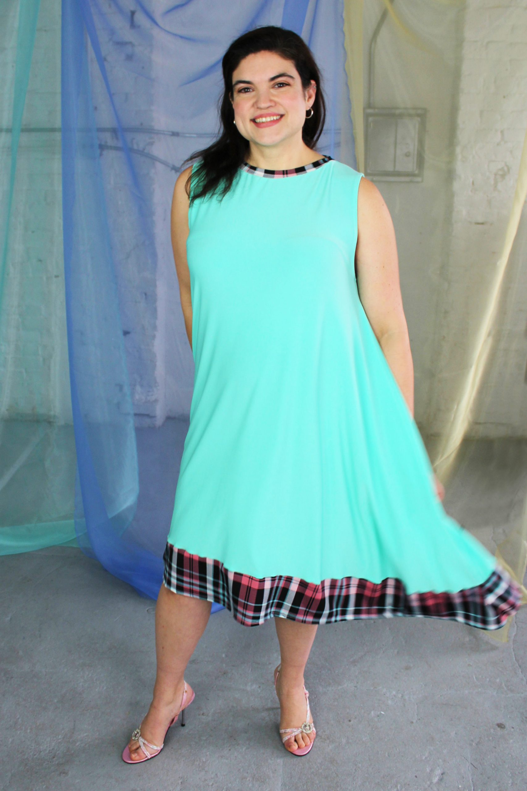 Inbetweenie white brunette model wearing seafoam blue green swing dress with pink plaid trim, ethically handmade in NYC