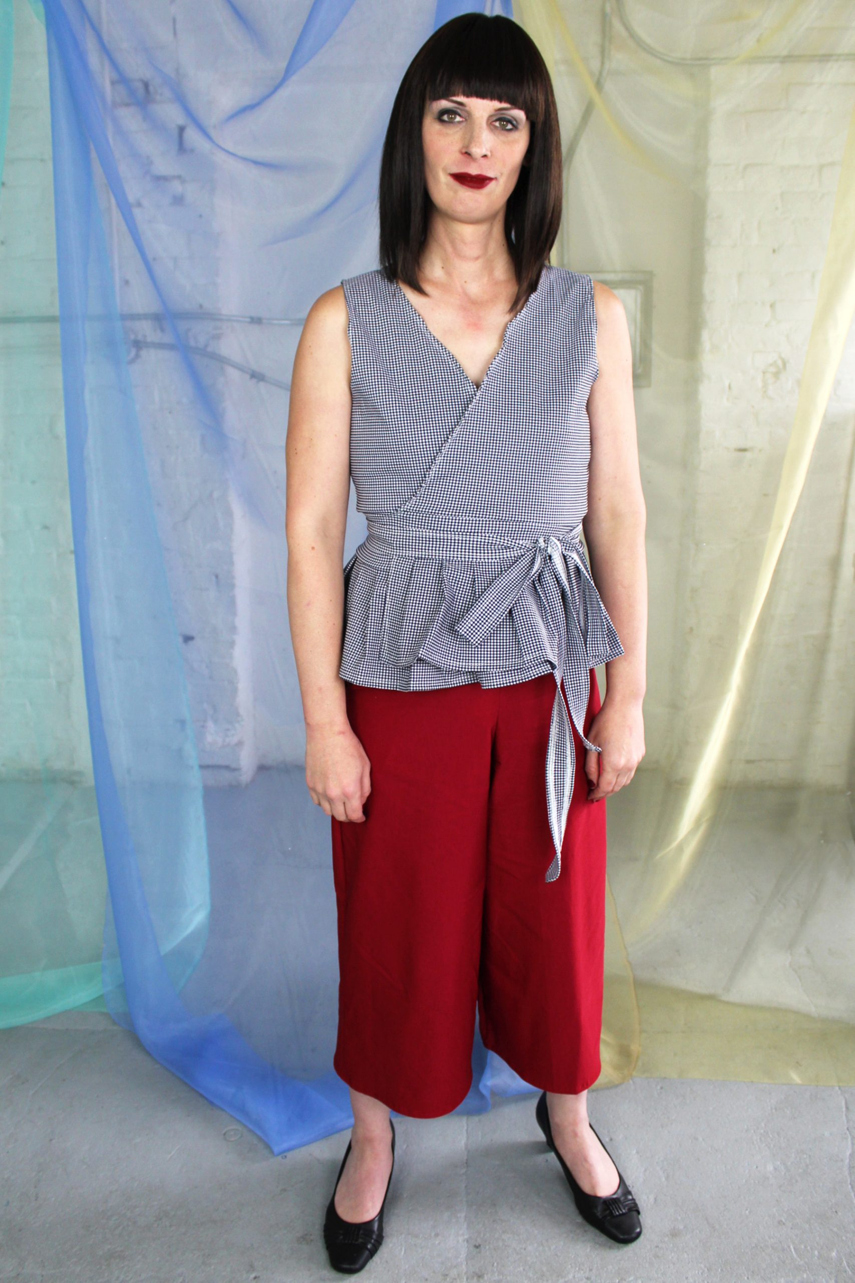 Straight size white brunette tall trans model in maroon red capri pants with pockets and black + white gingham check wrap top